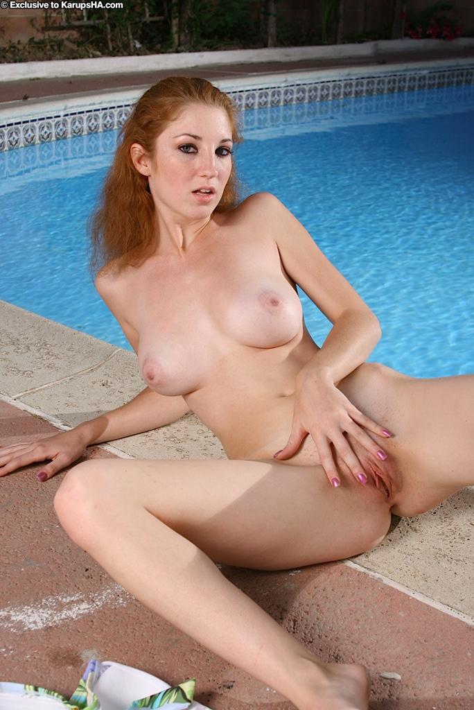 Рыженькая детка в трусах с огромной грудью и гладкой вагиной Stephanie Renee снимает одежду у бассейна