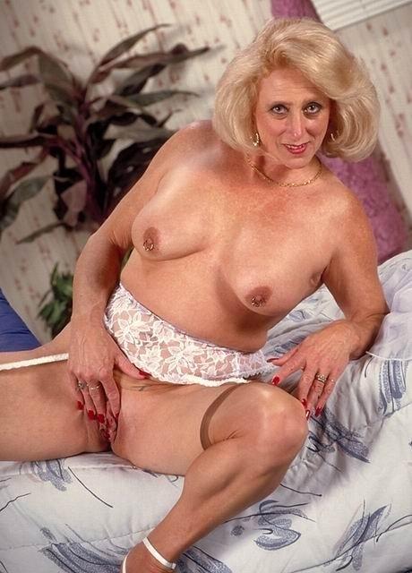 Нагая возрастная блондинка гладит свои сиськи в койке