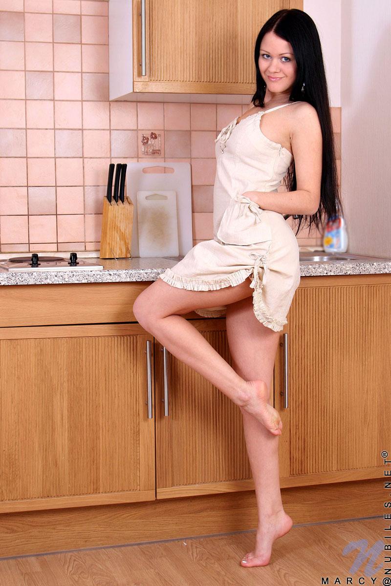 Темненькая девушка с шикарной грудью Marcy Nubiles снимает лифчик на кухне
