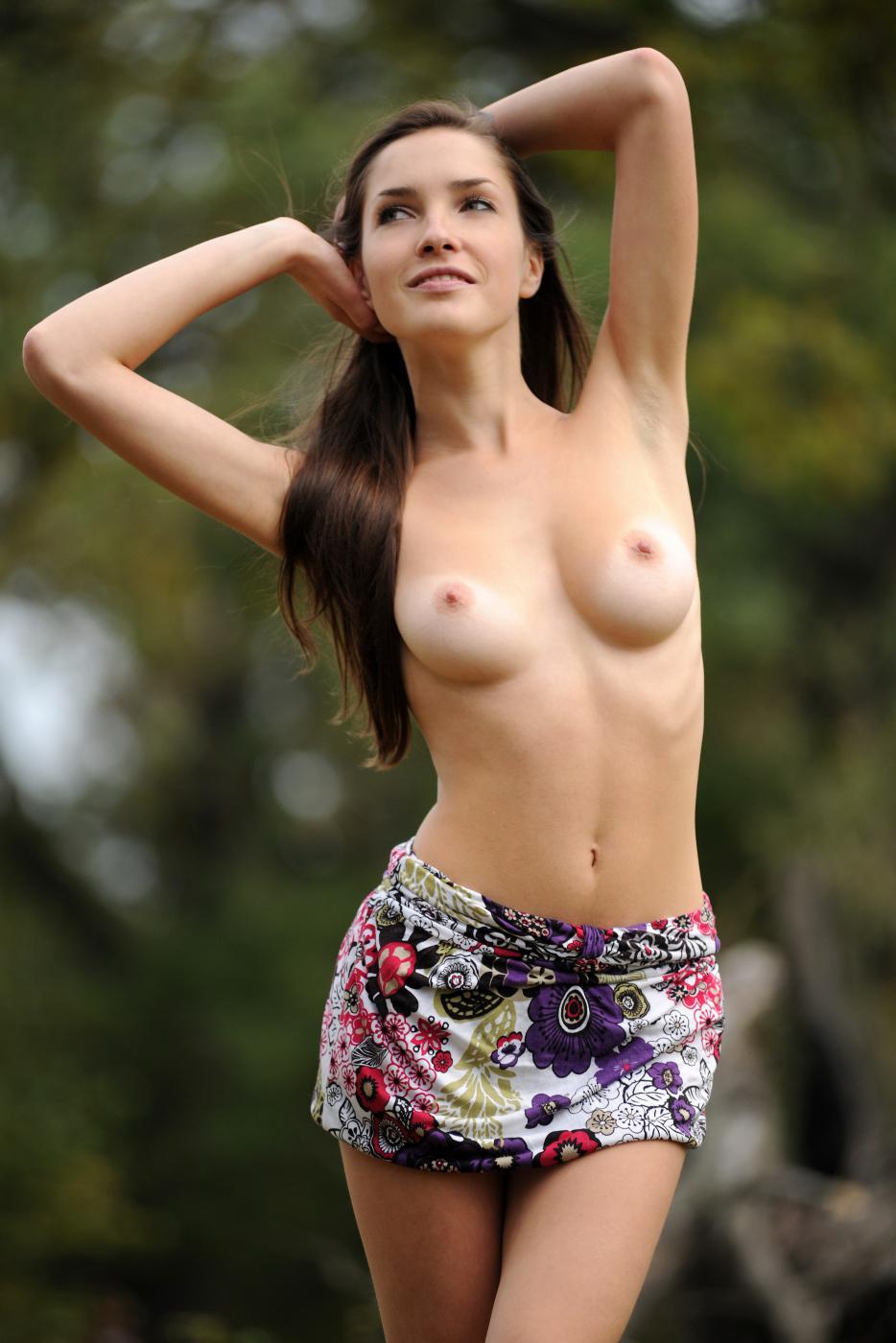 Сисястая темноволосая девка Semmi A идет на прогулку на луг и спускает свою одежду перед объективом