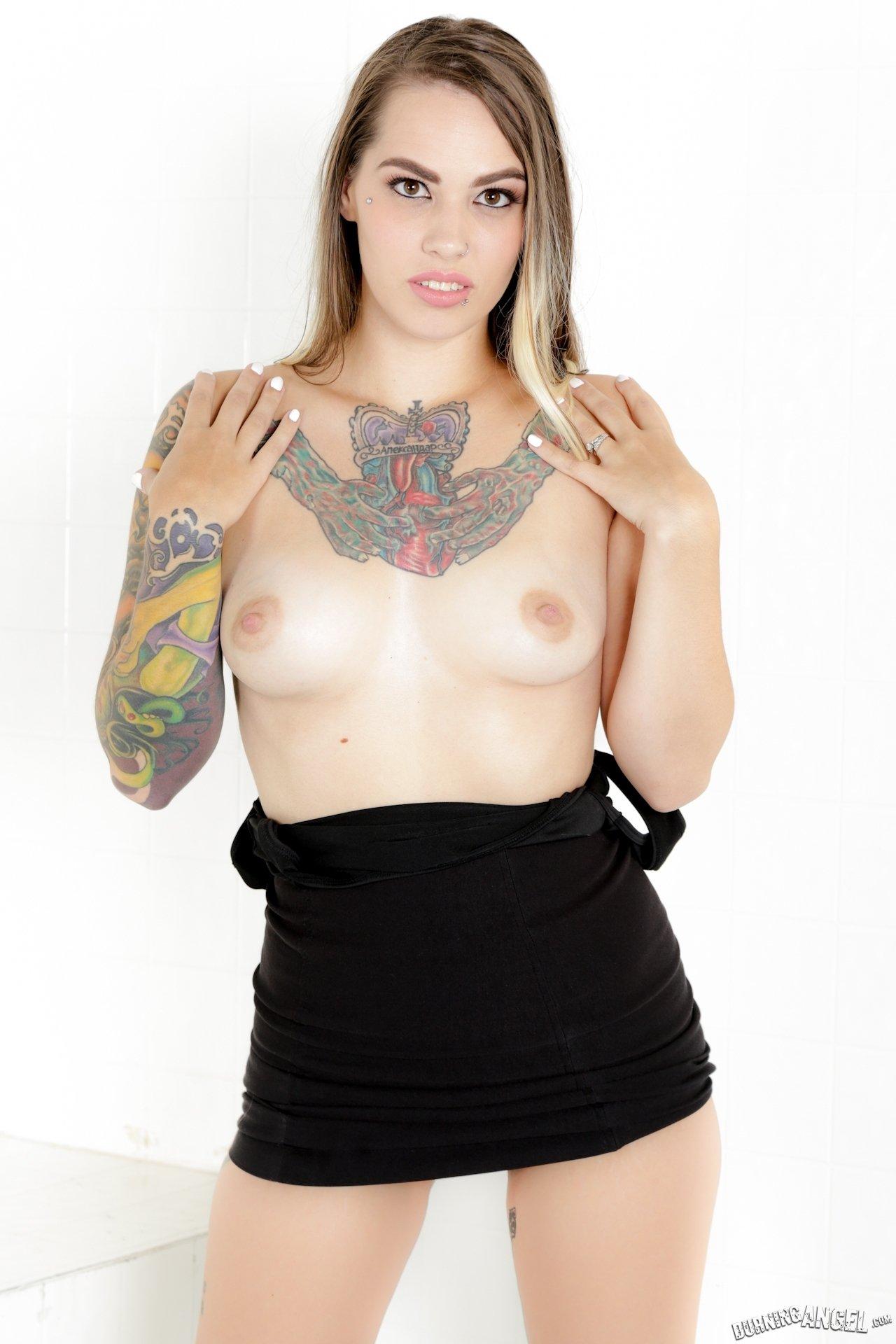 Изящная леди с широкой татухой на сиськи показывает киску