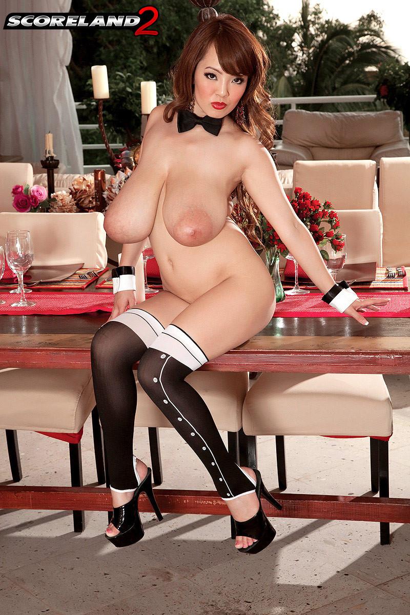Китаянка с большими дойками фотографируется на камеру вывалив их на стол