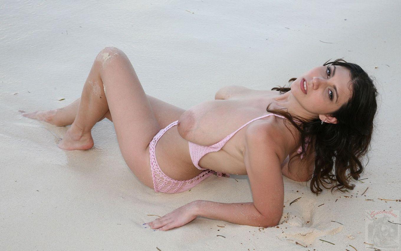 Темноволосая девка с натуральными титьками обнажает себя на песке – она действительно выглядит обалденно