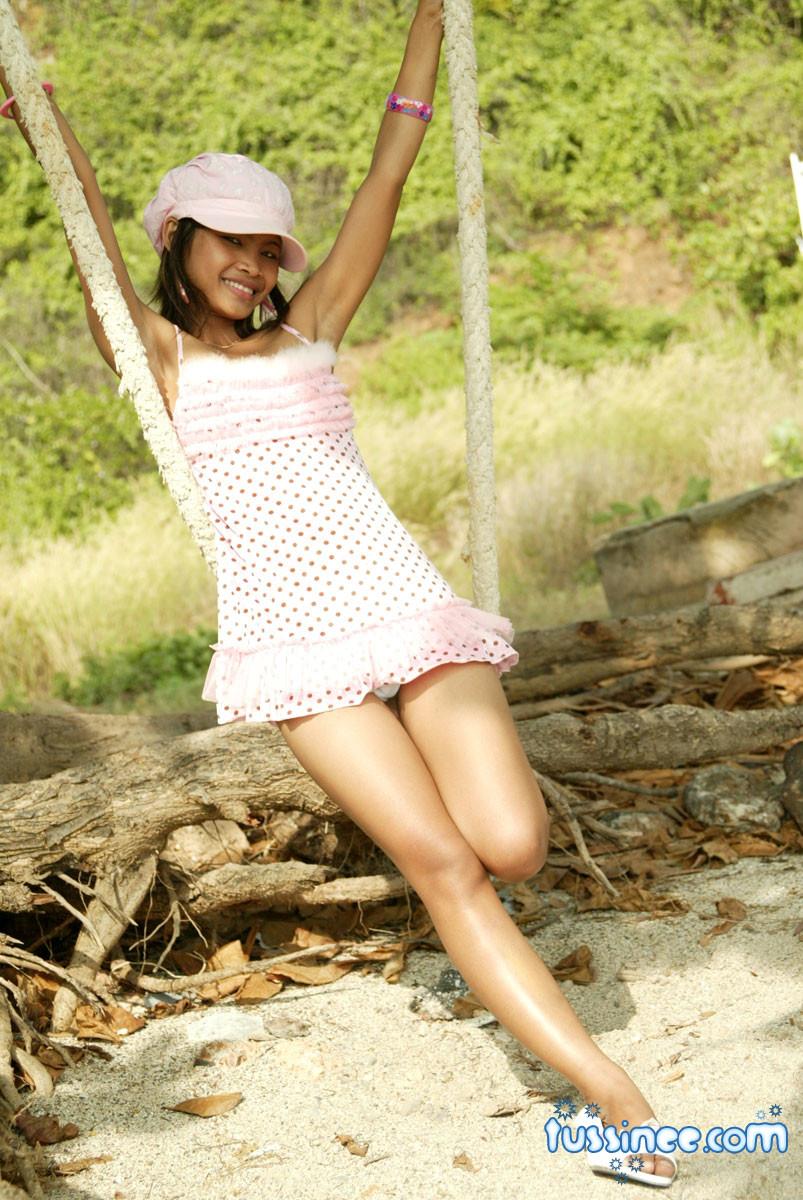 Девушка-азиатка качается на качелях и показывает свое хрупкое туловище, раскрывая некоторые интимные части