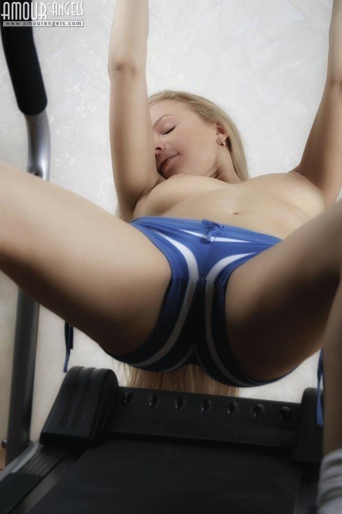 Гибкая светлая порноактриса Анюта занимается на тренажере голой, как только спускает шорты, так она чувствует себя свободней, тем более что выходит классное интимное соло