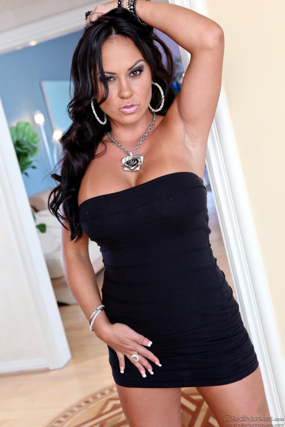 Титькастая девушка латинской внешности Мэрайя Милано позирует в маленьком черном платье и демонстрирует розовые стринги под юбочкой