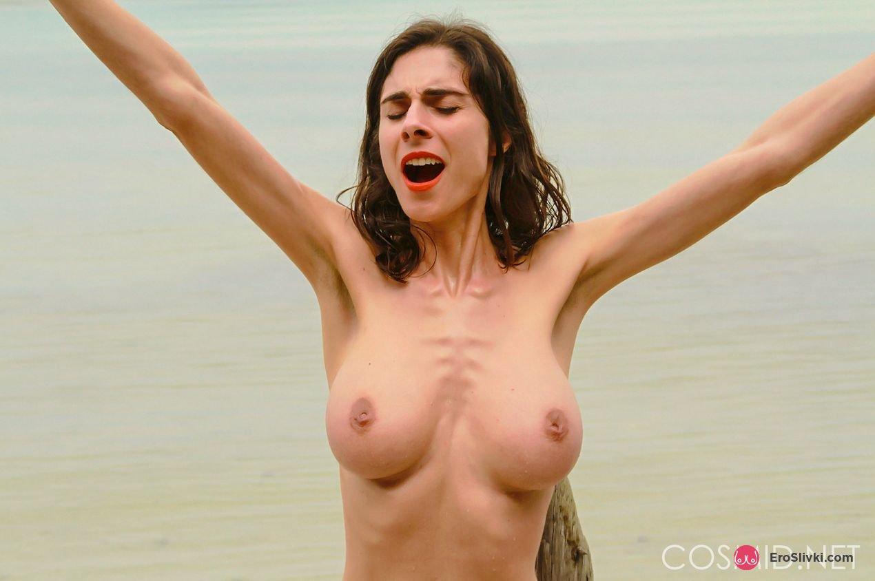 Голая модель с темными волосами на берегу моря оголила свои большие сиськи