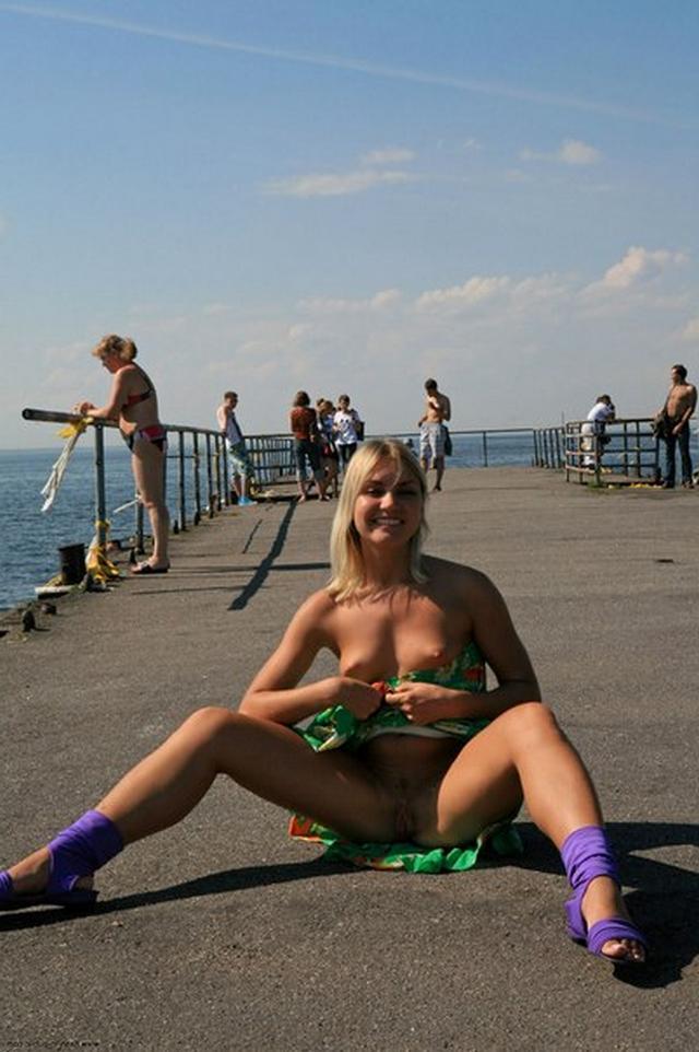 Блондиночка в фиолетовых шлепках прилюдно демонстрирует пизду и дойки