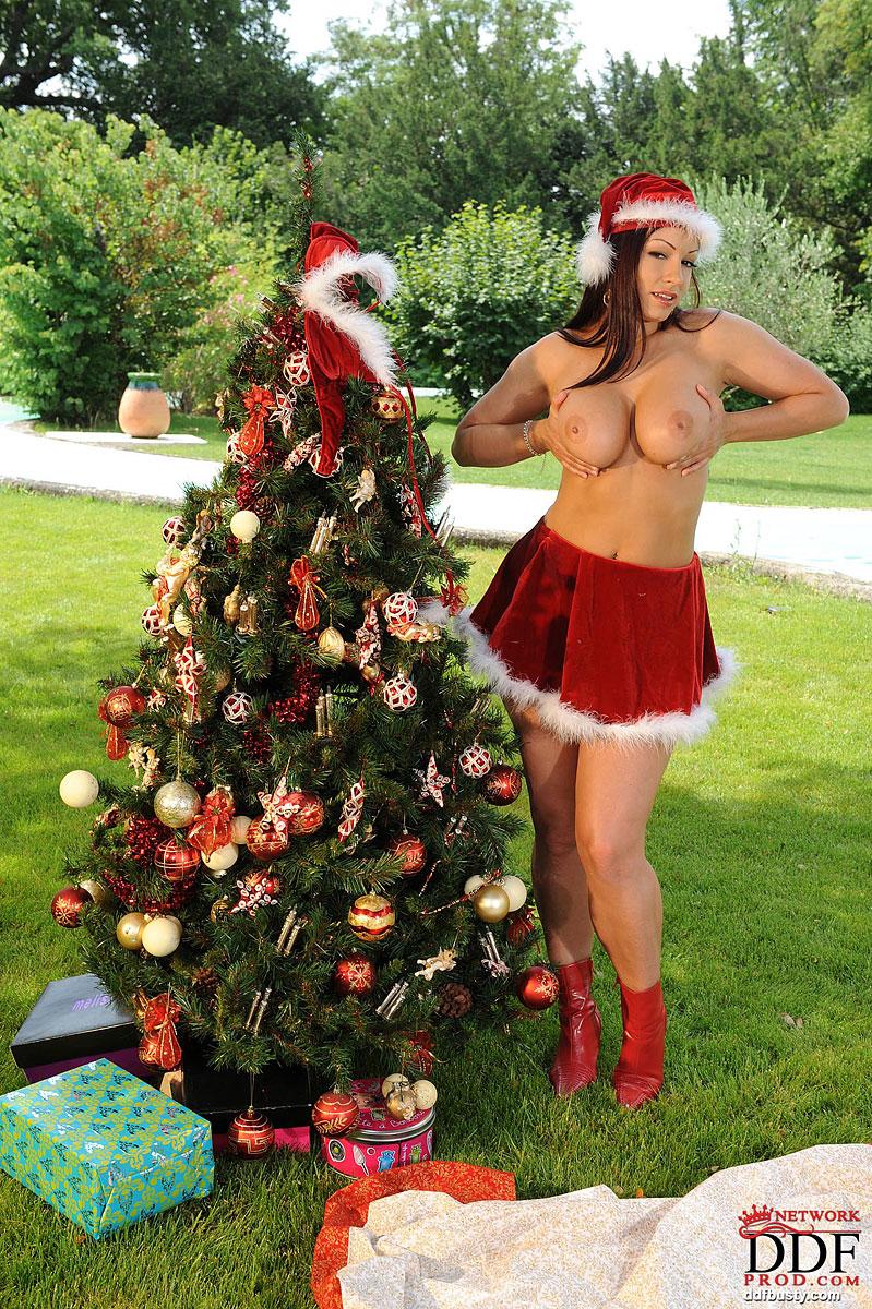Снегурочка с гигантскими дойками в красном костюме стоит около ёлки