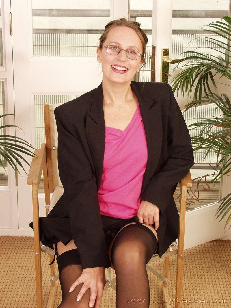 Секретарша в очках и черных нейлоновых гетрах Helena Onlytease демонстрирует стриптиз и оголяет свой кустик
